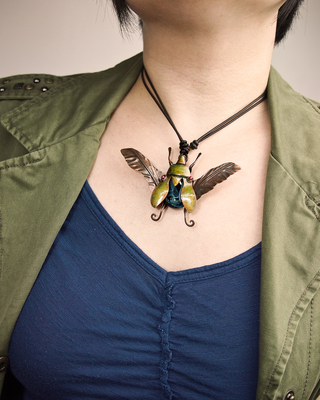 "Kharisma Sommers, Quincy, IL, U.S., ""Jewel Beetle"" (8.9 cm wide) ​(3.5 in wide) Copper, glass bead, leather, guilder's paste -- www.foldforming.org"
