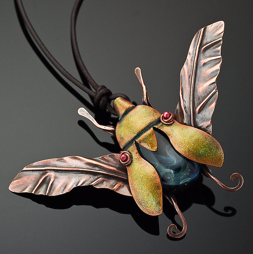 "​​Kharisma Sommers, Quincy, IL, U.S., ""Jewel Beetle"" (8.9 cm wide) ​(3.5 in wide) Copper, glass bead, leather, guilder's paste -- www.foldforming.org"
